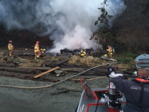 NKF&R firefighters use hoses deployed from the district's new fire-rescue boat and water from Hood Canal to battle a fire in a cabin that had no usable road access or fire hydrants nearby.
